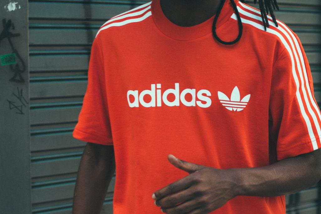adidasのブランドロゴが入ったTシャツを着ている男性の写真